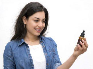 בחורה מחזיקה בקבוק שמן CBD