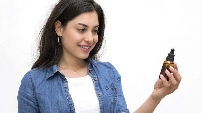 בחורה מחזיקה בקבוקון שמן CBD